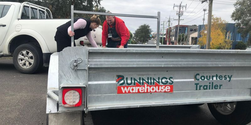 Bunnings team member helping a customer load onto a trailer.