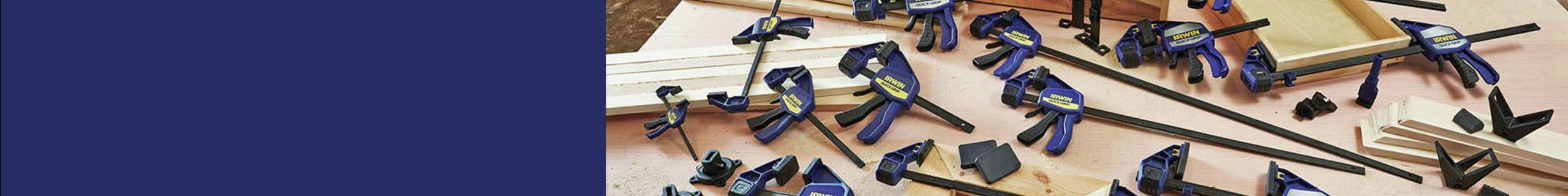 Multiple Irwin quick-grip clamps sprawled across a workbench and surrounded with timber