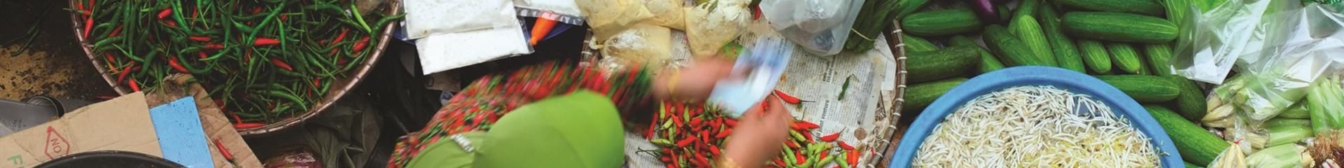 Top view of a person sorting through various vegetables including chilis