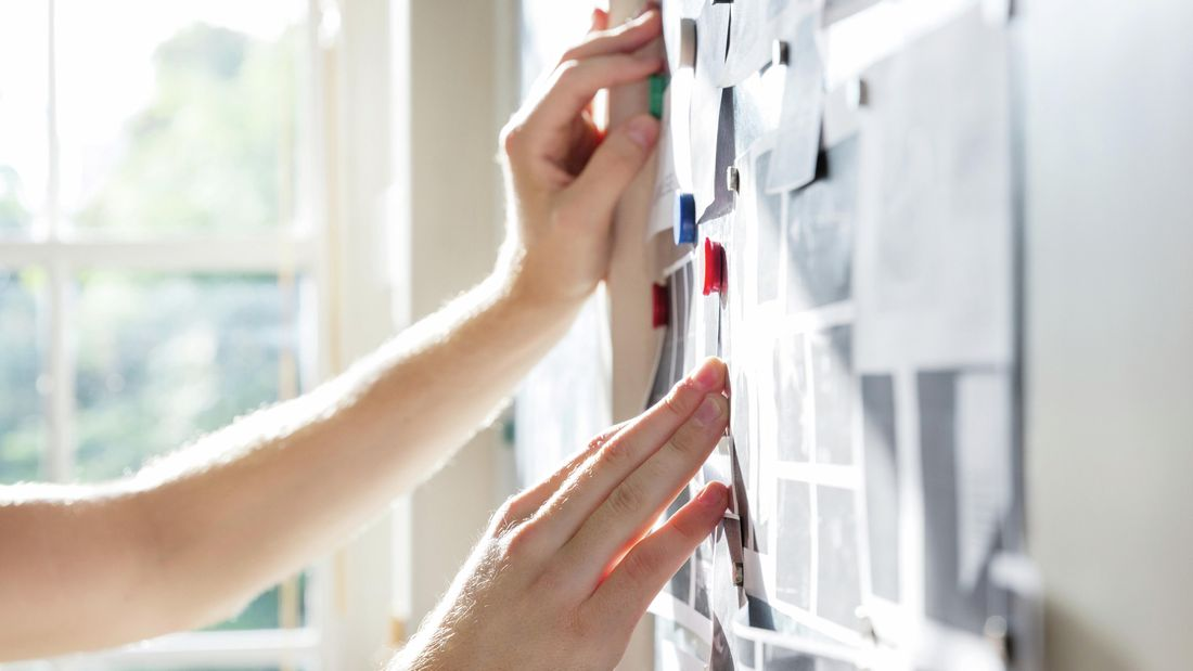 Close-up of hands on a wall planner covered in notes and photos
