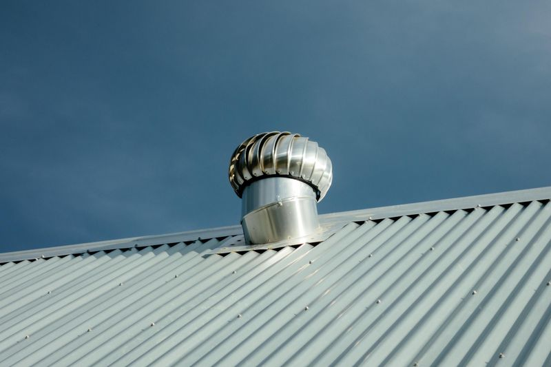 Close up shot of a roof vent on a tin roof with a deep blue sky in the background