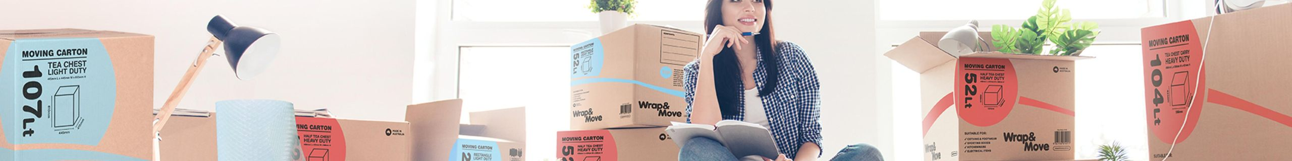Woman sitting on the floor in a room with a notepad and pen, surrounded by moving boxes