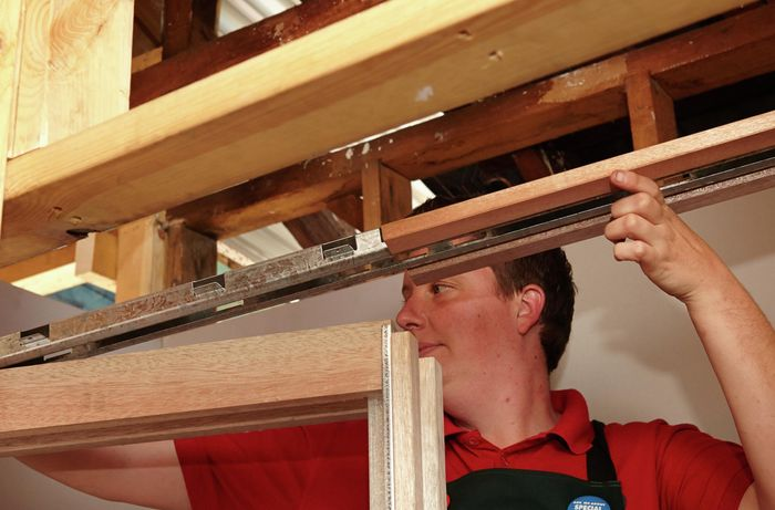 A person assembling a sliding door frame
