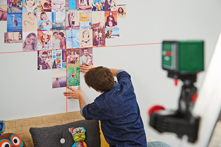Person using laser level to hang pictures