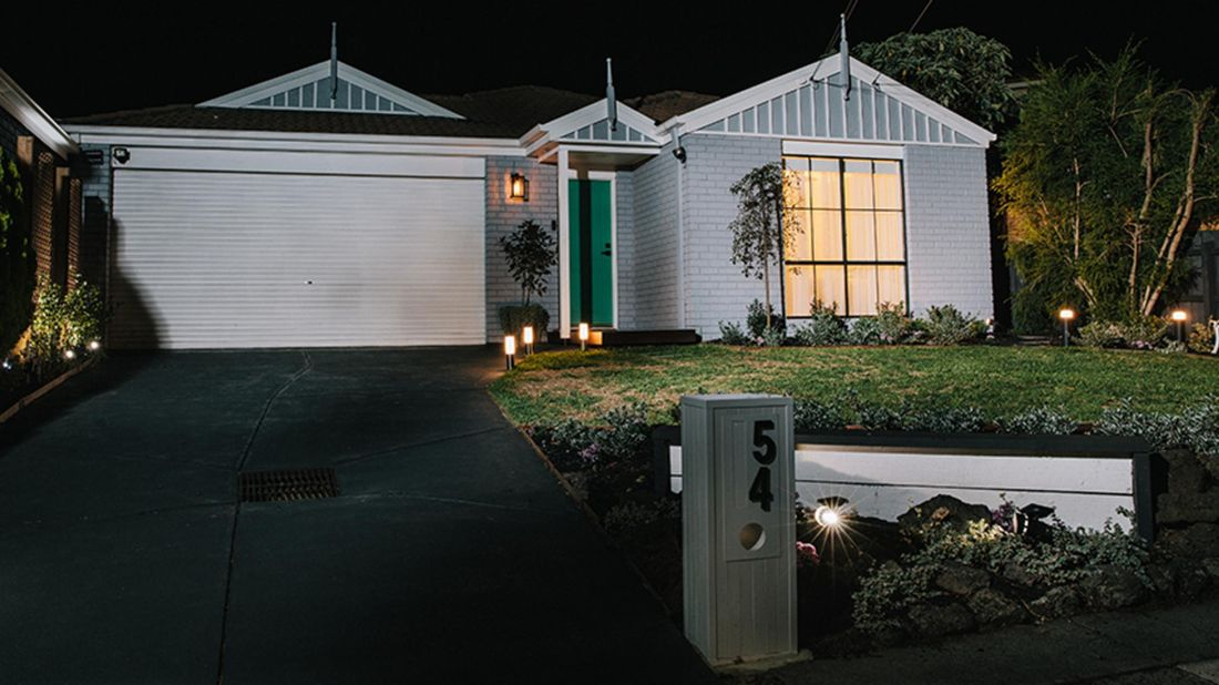 Wide shot of a grey brick house at night, with several garden lights placed around the garden bed, footpath and mailbox