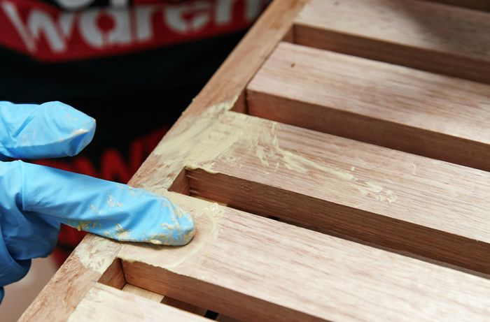 Person filling gaps in timber slat and frame with putty