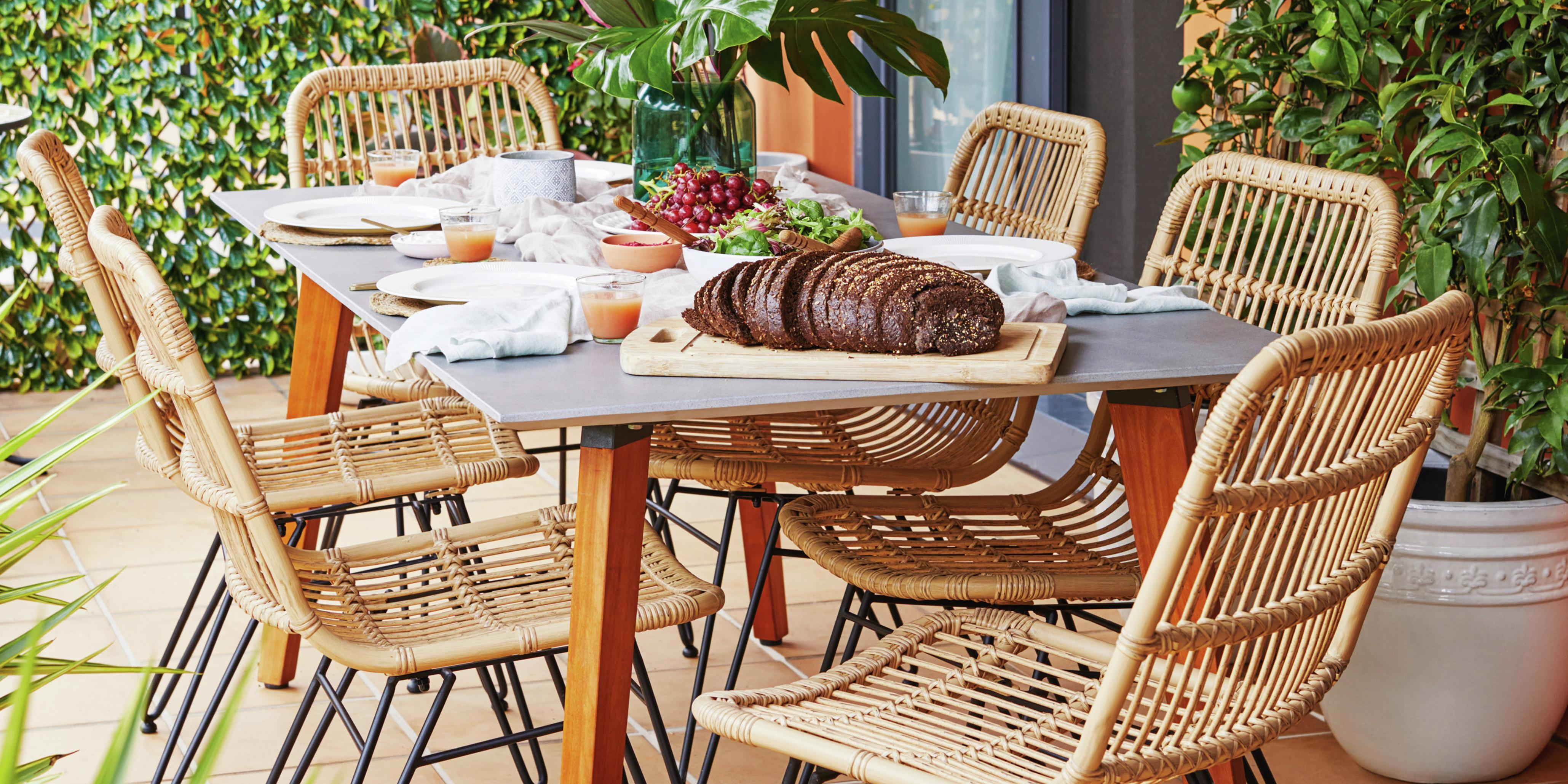 Outdoor dining area with dining table, chairs and potted plants