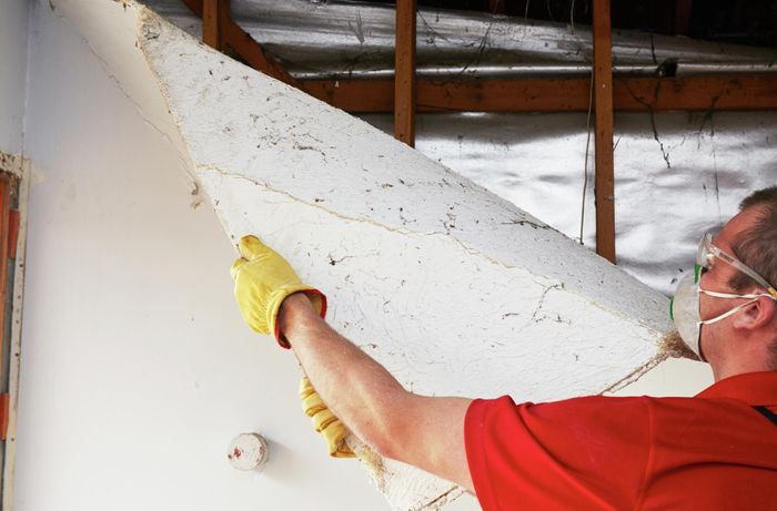 A person wearing protective gear pulling a sheet of plaster off a stud wall