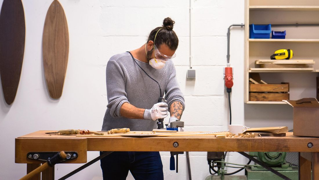 Man using a rotary tool to carve wood, with 2 wooden surfboards hanging on the wall in the background