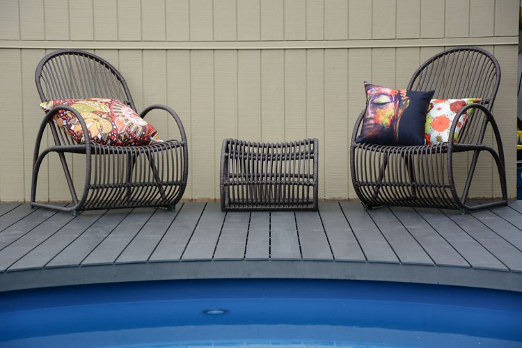 Pool surrounded by timber decking with two chairs