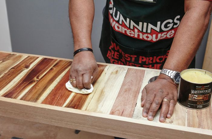 Person waxing the table
