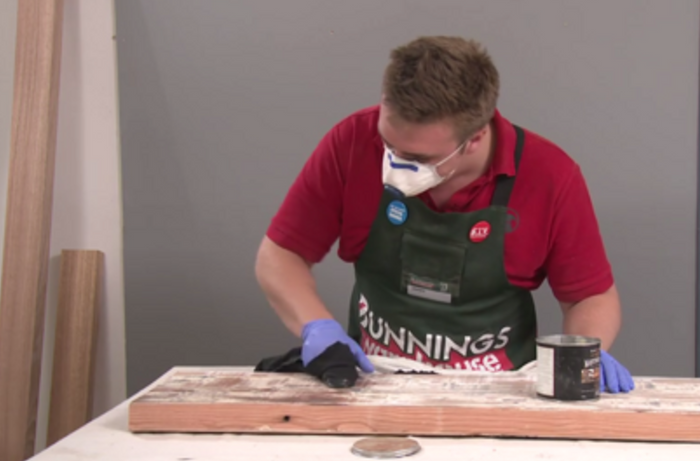 A Bunnings team member waxing a piece of timber