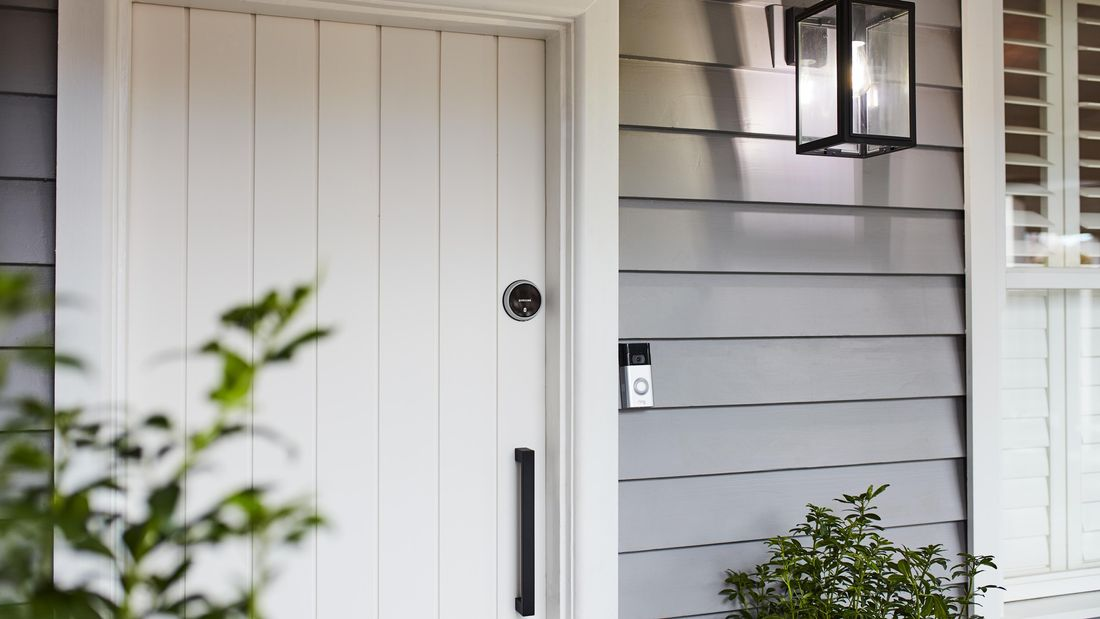 White front door in a blue weatherboard house.