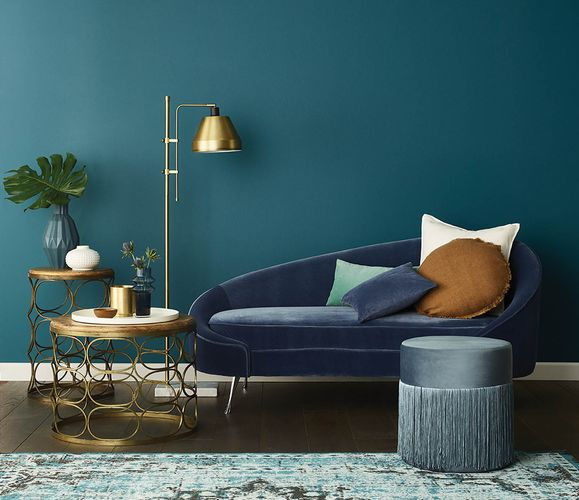 Sofa, lamp and side tables against a blue wall