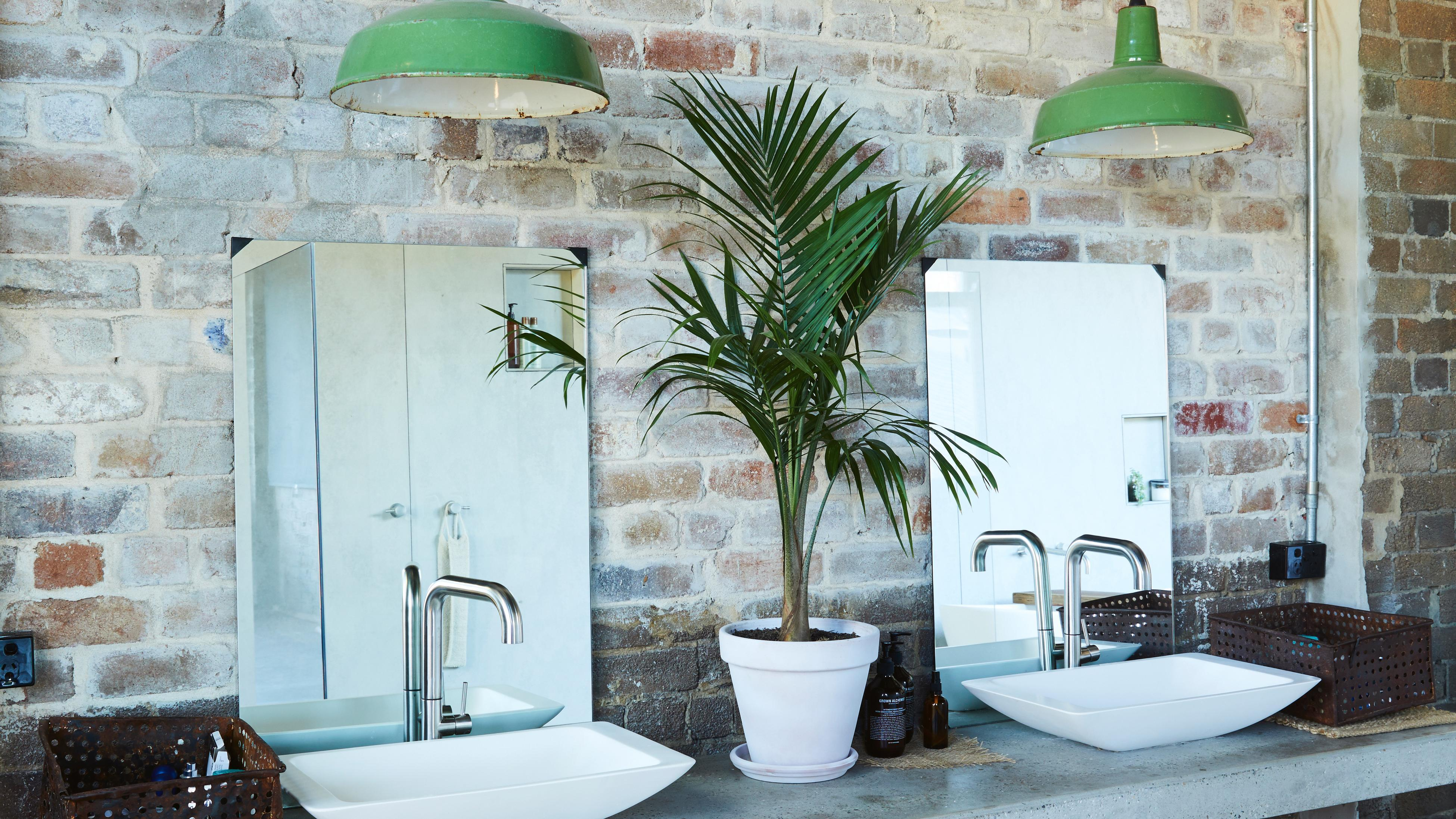 Exposed brick wall bathroom with two sinks