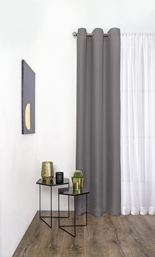 Interior of a modern living room with sheer and dark grey curtains on a metal curtain rod over the window