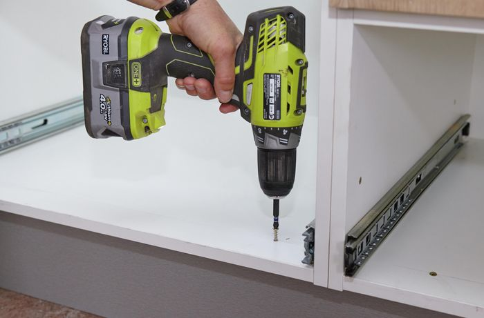 A person inserting a screw through the bottom of a cabinet into the kickboard