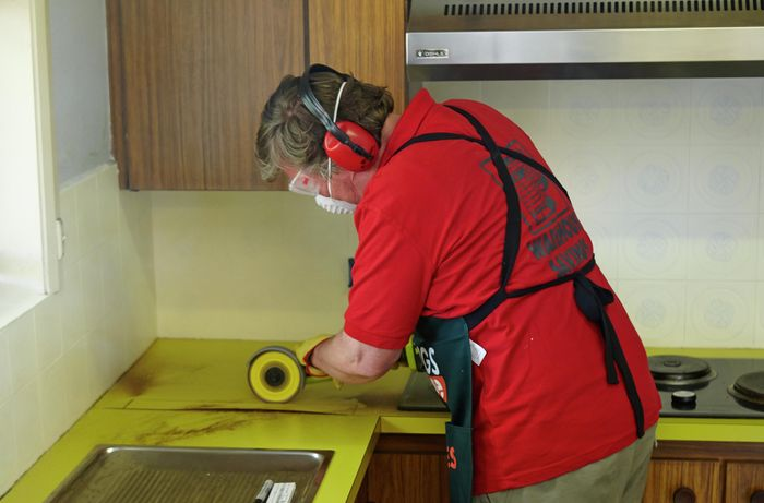 Person using a handsaw on a benchtop.