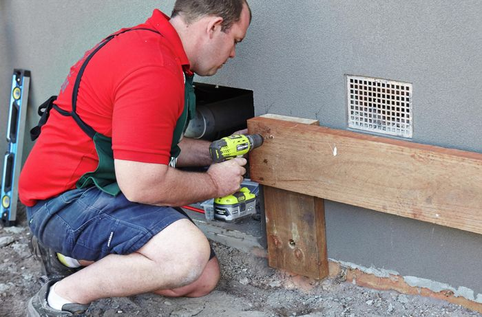 Person drilling timber sleeper to timber support post against the wall.