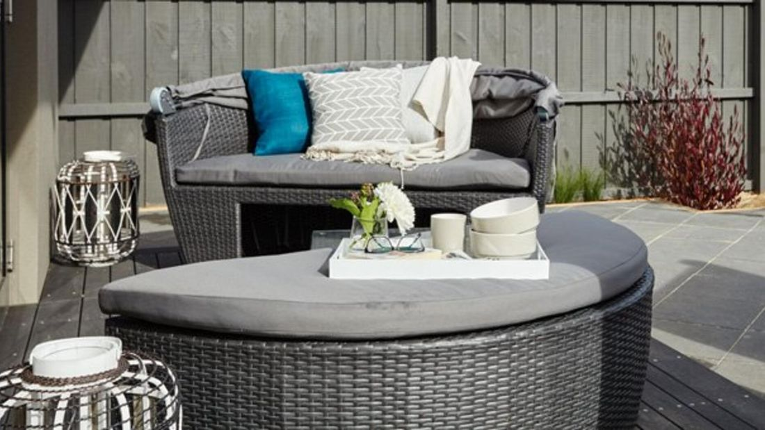 Outdoor couch with cushions and blankets.