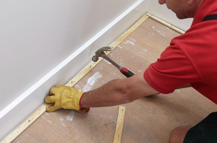 A perimeter of smooth edge being nailed down to subfloor by a Bunnings team member