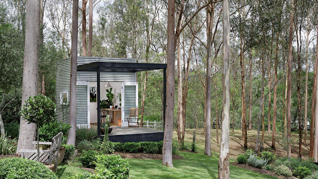 Small building clad in Colorbond with deck and French doors in a bushland garden