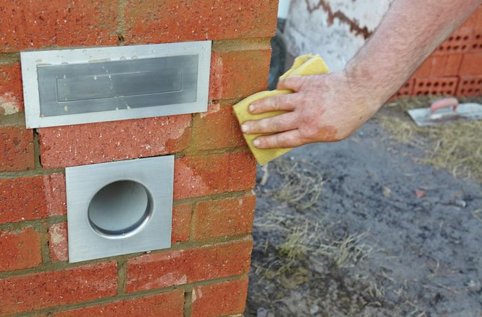 Excess concrete being cleaned off the sides of a brick letterbox