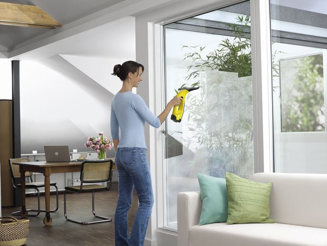 Woman using window vacuum to clean windows
