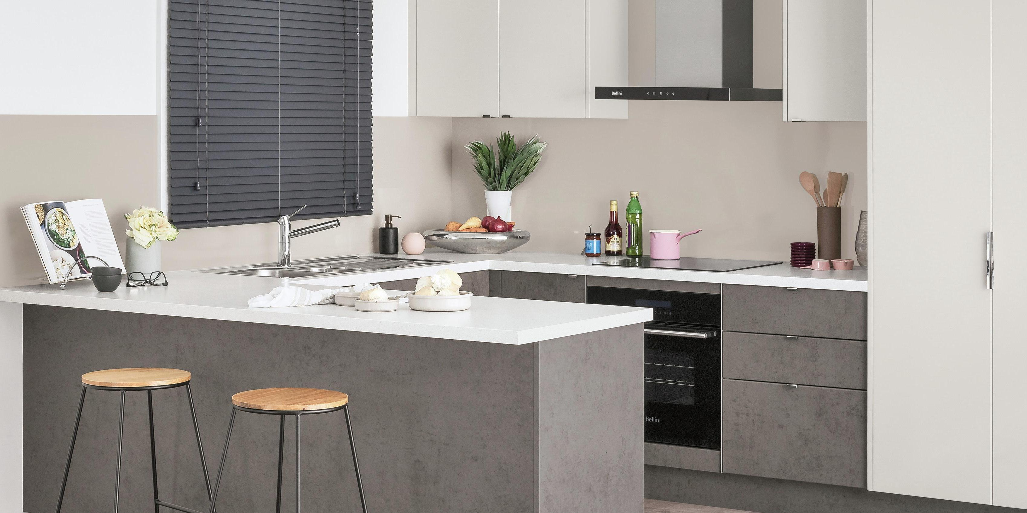 Kitchen with U-shaped kitchen benchtops, stainless steel sink and two stools