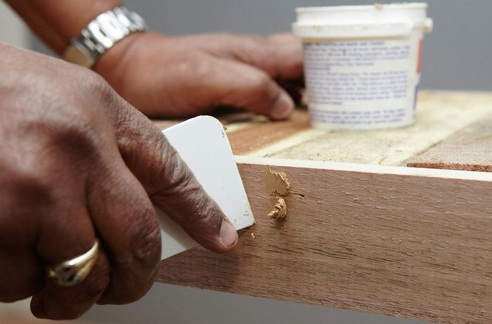 Person apply putty to cover nail holes