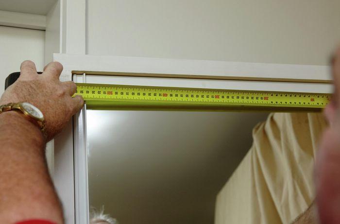 A person measuring the width of a wardrobe mirror door