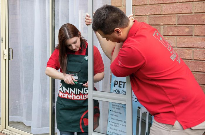 Two people working together to screw a doggy door together.