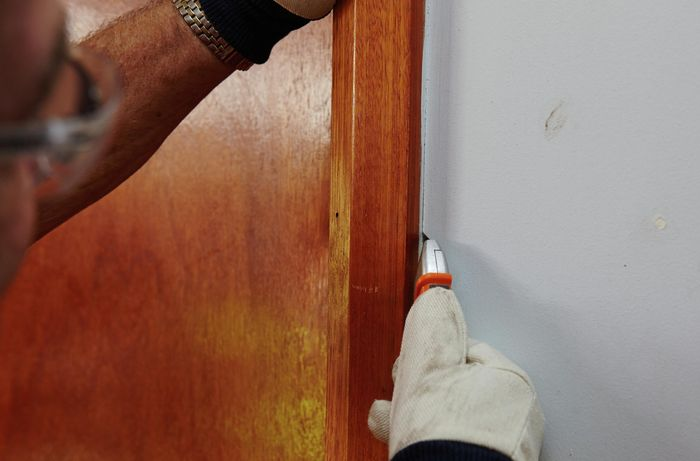 Person using a box cutter to create a gap between architrave and wall.