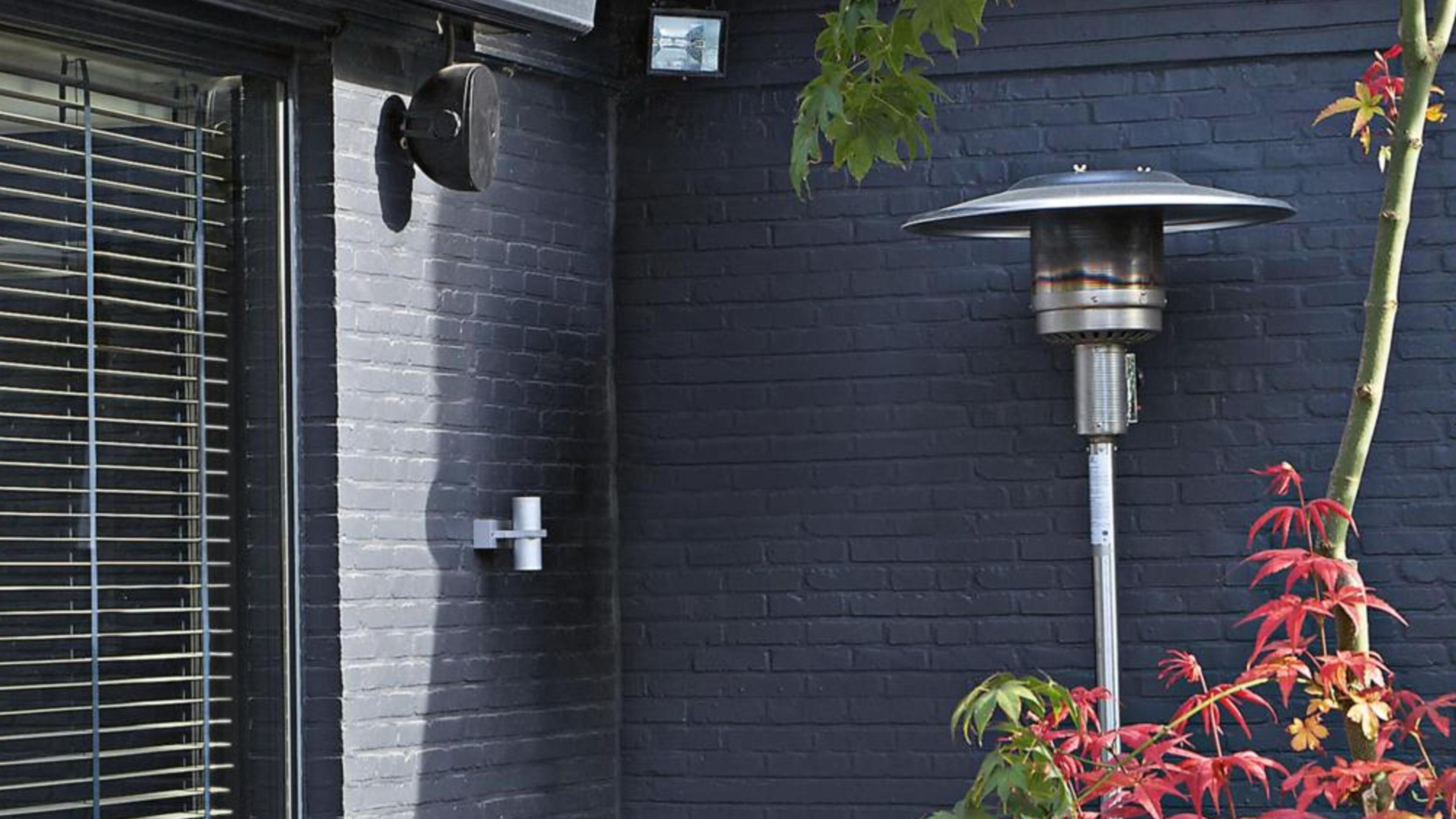 The Fiammetta outdoor gas patio heater outside a dark grey house.