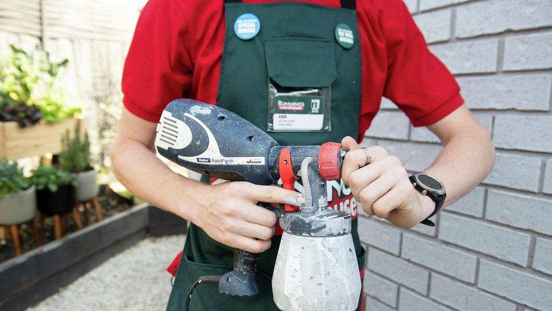 A Bunnings team member holding a paint sprayer