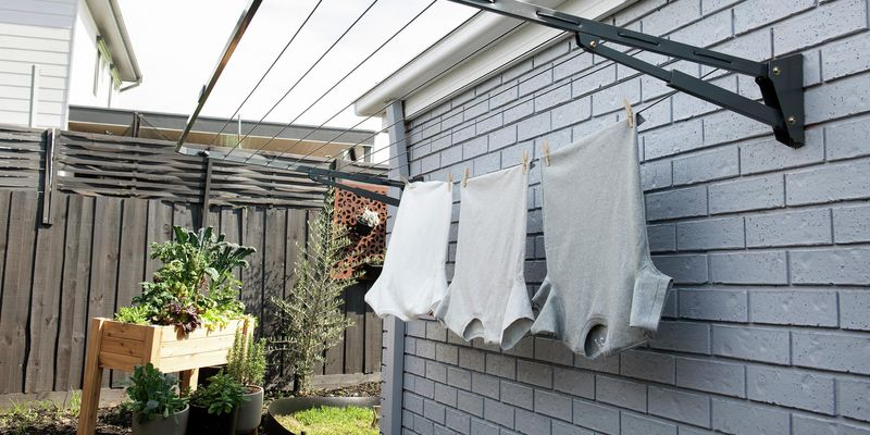 T-shirts hanging from a wall-mounted clothesline.