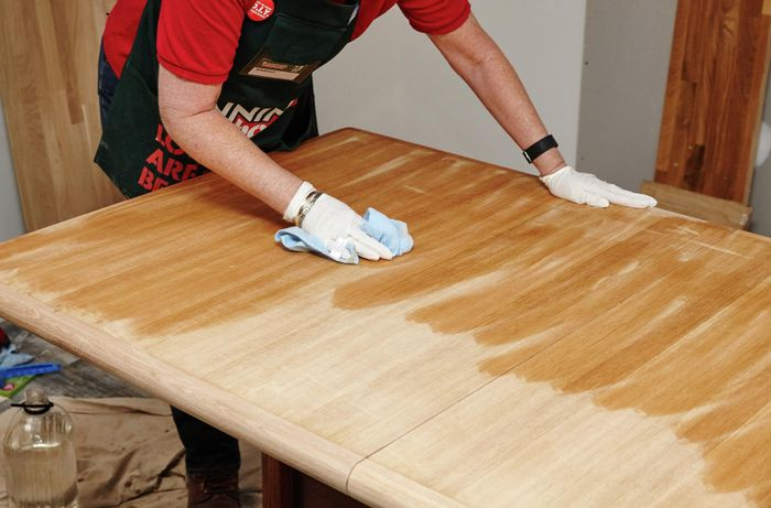 Bunnings Team Member wiping the table with turps