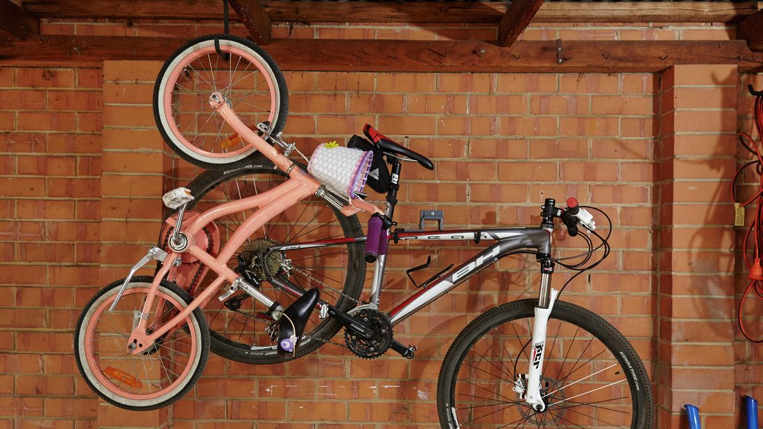 Two bicycles hanging from hooks in a garage