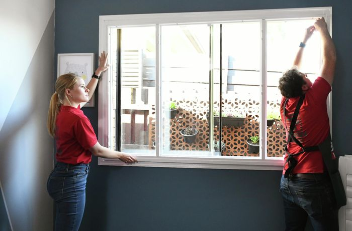 Two people holding a plantation shutter frame against a window