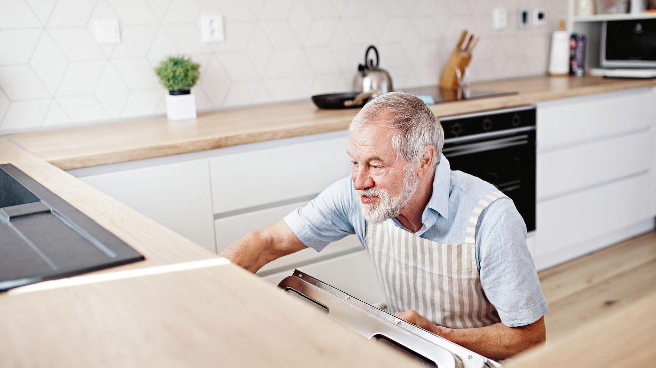 Man in striped apron opens over door.