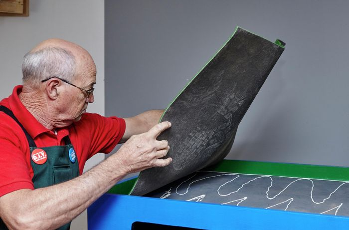 Person gluing felt to table top