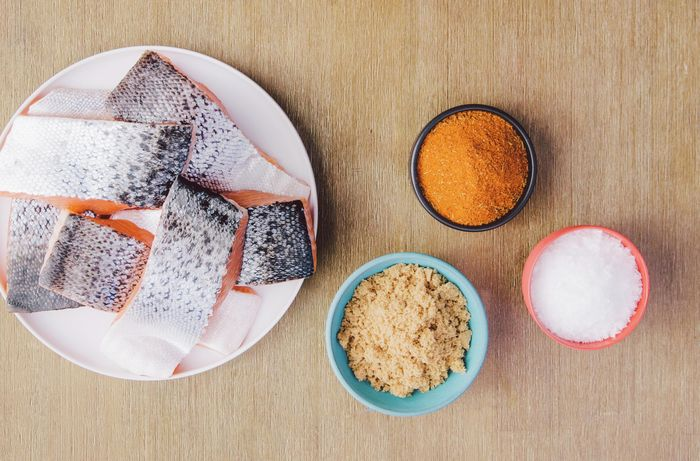 Fillets of salmon on a plate next to bowls of spices