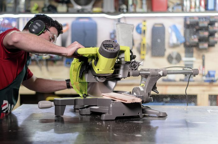Bunnings team member showing how to use a mitre  saw