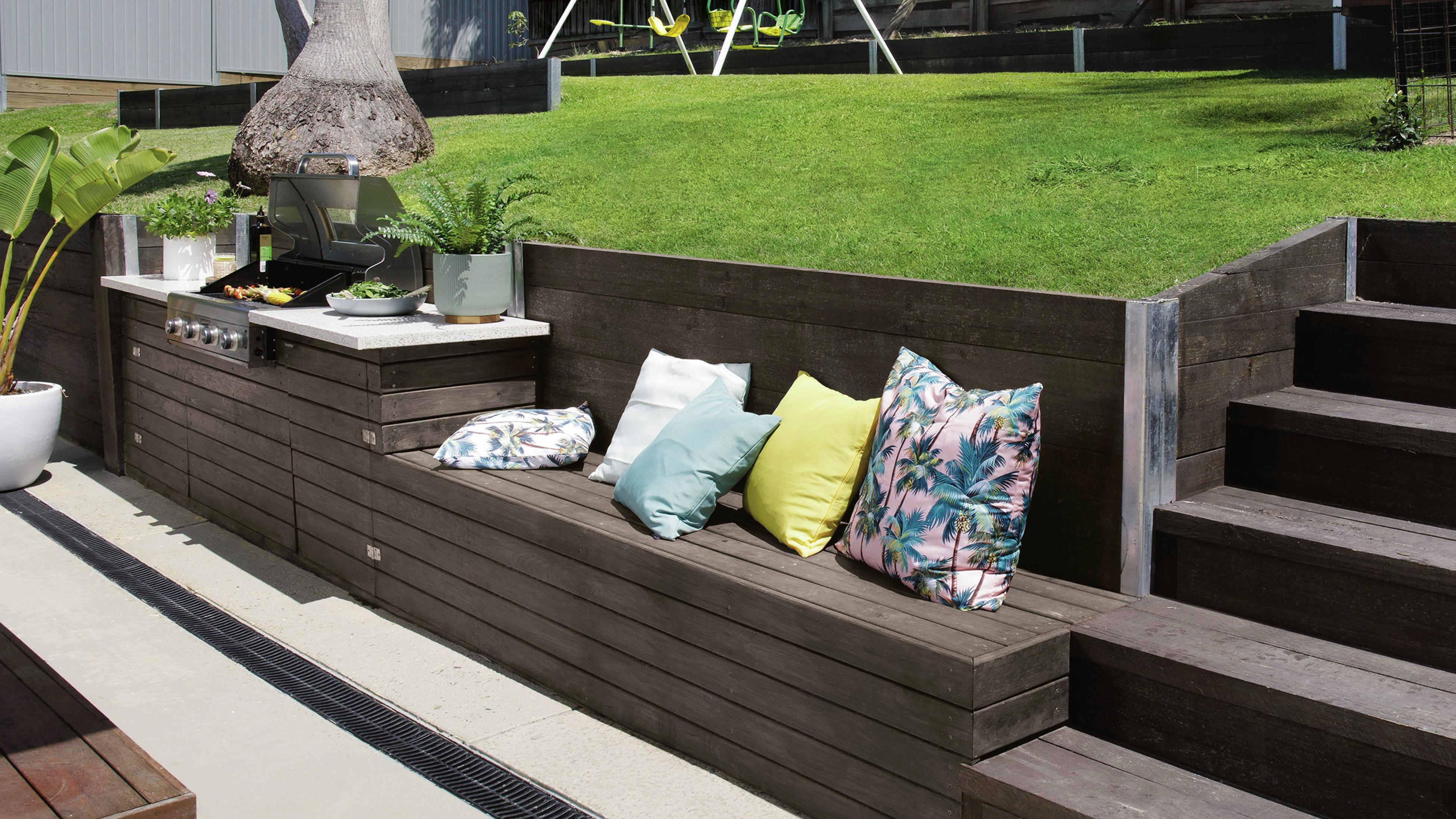 Seating in an outdoor setting cut out of lawn slope with throw cushions