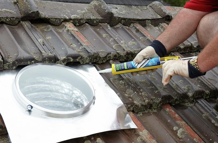 Silicone gap filler being used to waterproof the skylight flashing's edge with the roof tiles below