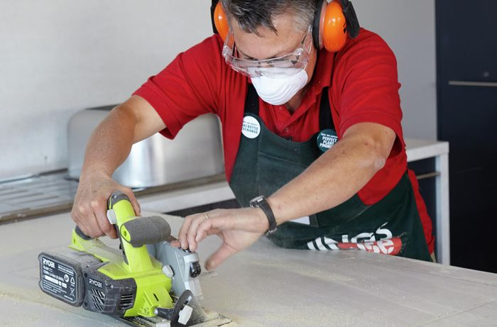 Person cutting kitchen benchtop with handsaw.