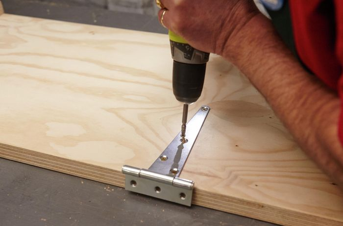 Person attaching hinge to timber with drill.