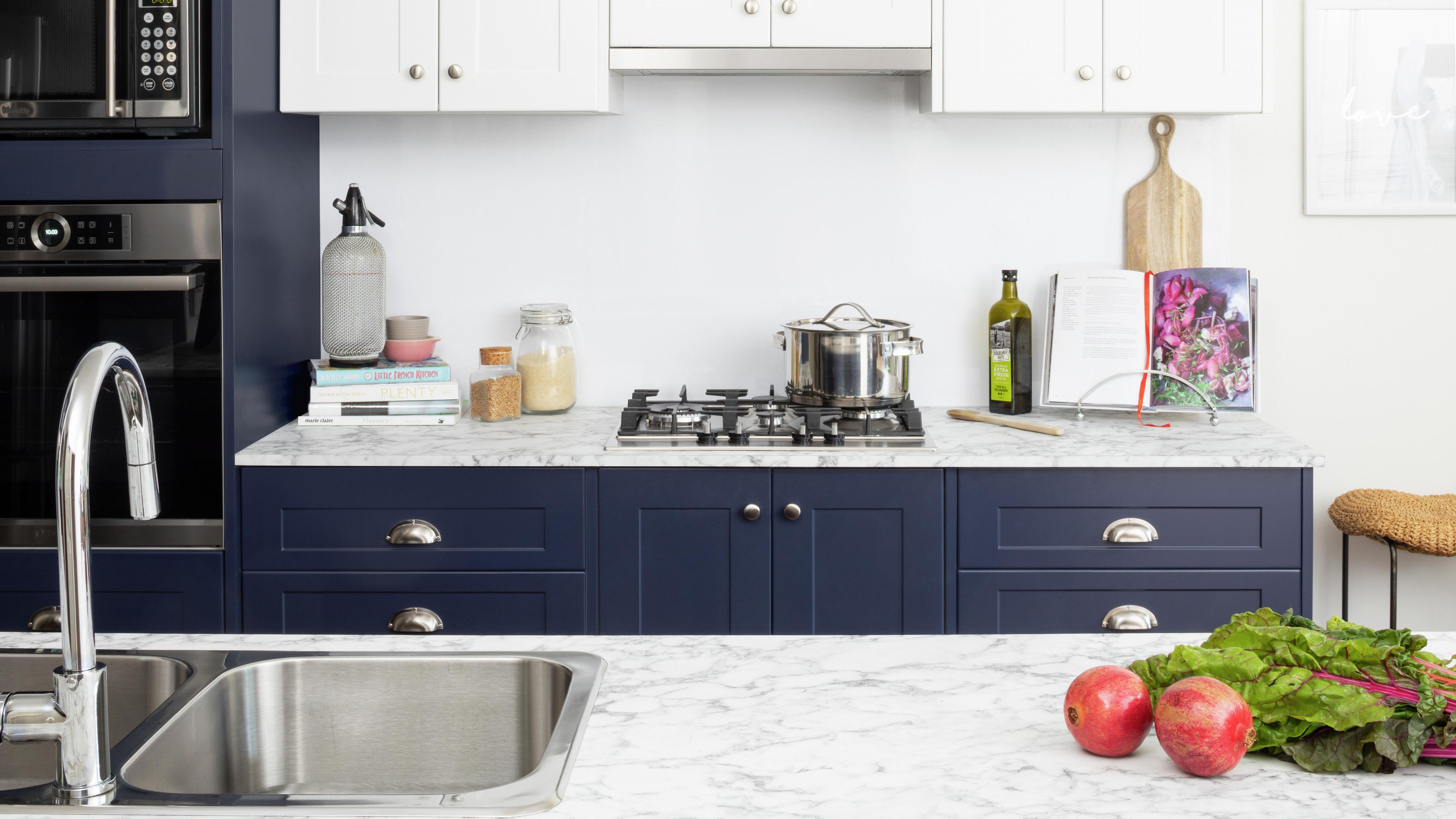 Kitchen with blue and white cabinets and a marble benchtop.