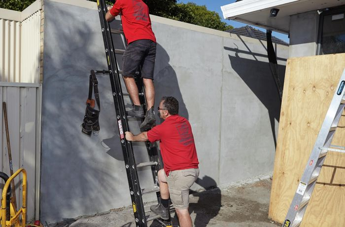 One man holding an extension ladder against a wall while another man climbs