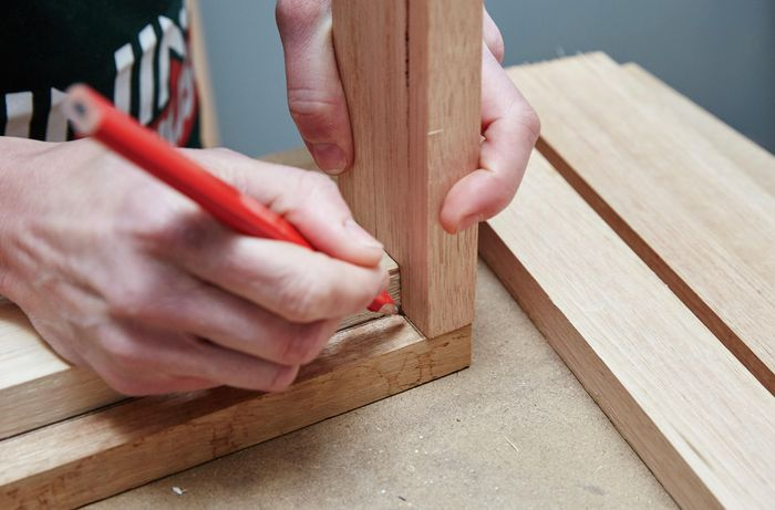 Person marking joins of two pieces of timber with pencil
